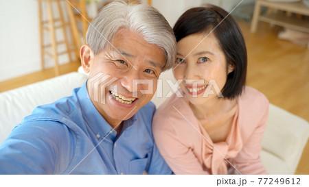 リビングで自撮りをするミドル夫婦 77249612