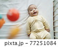 Happy Smiling Asian Newborn baby boy lying on bed or cot having fun playing with mobile. 77251084
