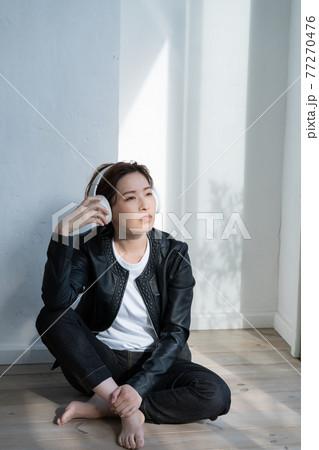 床に座って音楽を聴く革ジャンを着た女性 77270476