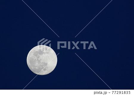 空に浮かぶ煌々と光る満月 77291835