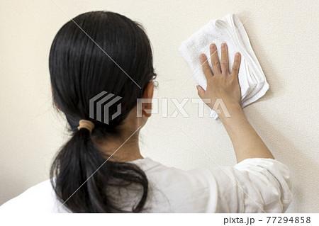 タオルで壁を拭き掃除する女性の手 77294858