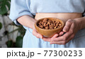 Woman holding bowl of almonds 77300233