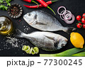 Two uncooked dorado fishes on black background with spices and vegetables 77300245