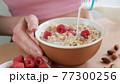 Pouring milk in oatmeal muesli 77300256