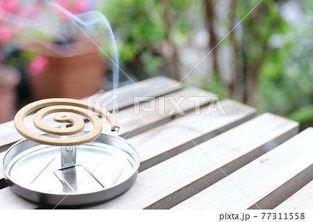 縁側に置いてある煙のたっている蚊取り線香 77311558