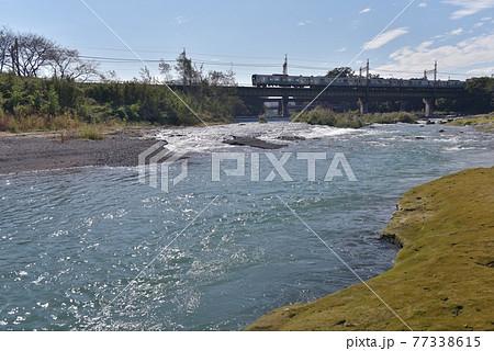 秋のまだ強い光を反射する入間川の流れを渡る、西武線30000系スマイルトレイン 77338615