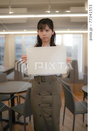 怒った顔でホワイトボードを持つ女性 77341553