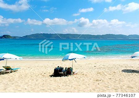 【沖縄】座間味島 ビーチパラソルが並ぶ砂浜とエメラルドグリーンの海 77346107