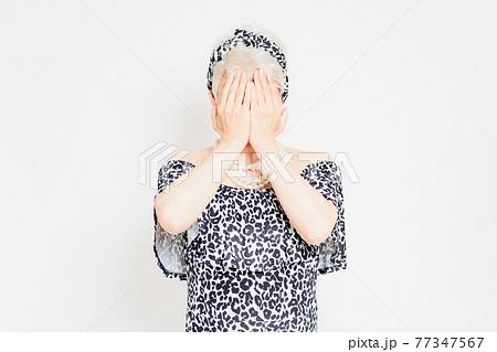 白背景の前に立って、顔を隠すドラァグクイーン 77347567