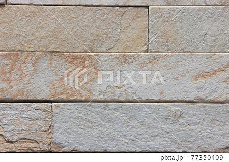 細長く加工された岩石を並べた壁のクローズアップ 77350409