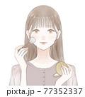パウダリーファンデーションをメイクブラシで顔に塗る女性 77352337