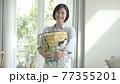 洗濯かごを持つ女性 77355201