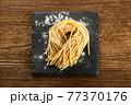 Raw handmade spaghetti pasta on board with flour 77370176