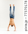 Athletic man in jeans with bare chest performing handstand 77370178