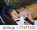 粉ミルクを飲むベビーカーに乗っている赤ちゃん 77375332