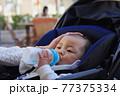 粉ミルクを飲むベビーカーに乗っている赤ちゃん 77375334