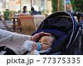 粉ミルクを飲むベビーカーに乗っている赤ちゃん 77375335