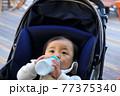 粉ミルクを飲むベビーカーに乗っている赤ちゃん 77375340