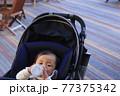 粉ミルクを飲むベビーカーに乗っている赤ちゃん 77375342