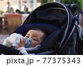 粉ミルクを飲むベビーカーに乗っている赤ちゃん 77375343