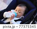 粉ミルクを飲むベビーカーに乗っている赤ちゃん 77375345