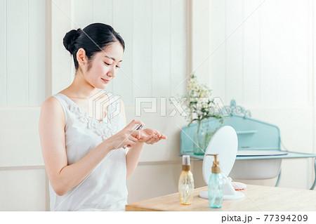 香水・虫除けをつける女性 77394209