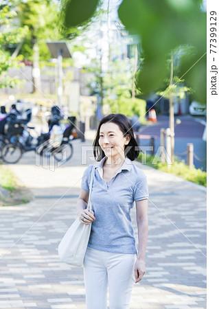 リラックスした表情で散歩する中年女性 77399129