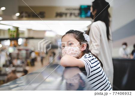 マスクを着用して買い物をする親子 77406932