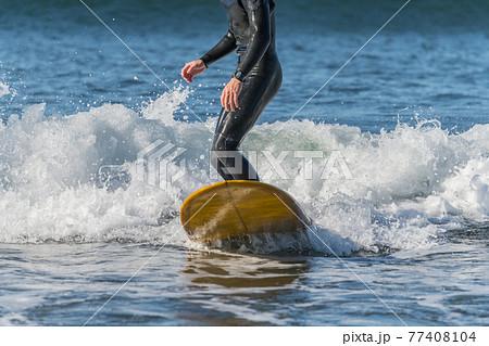 【強風吹き荒れる春の嵐の中のサーフィン】 77408104