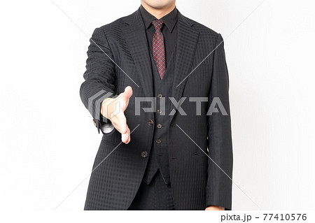 白背景の前に立って、握手のジェスチャーをする男性ビジネスマン 77410576