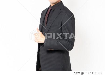 白背景の前に立って、いいねのジェスチャーをする男性ビジネスマン 77411302