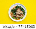 White plate of fried flat noodle with pork and kale in gravy sauce on yellow background. 77415083