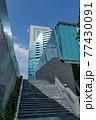 ガラス張りのモダン建築と階段と青空 77430091