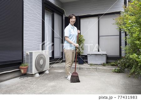 駐車場の掃き掃除をするハウスクリーニング の女性 77431983