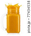 mason jar of splashing mango smoothies isolated on white 77434538