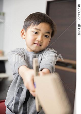 手作りの玩具の剣でで室内遊びをする小学生男の子 77447736
