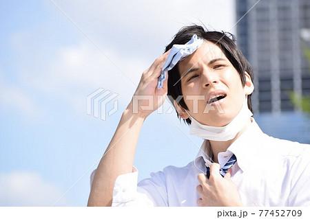 暑くてマスクを外してハンカチで汗を拭いている若い男性 77452709