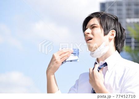 暑くてマスクを外してハンカチで汗を拭いている若い男性 77452710