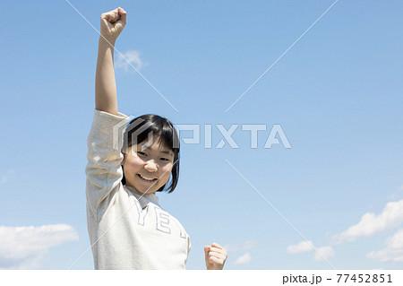 青空の下でこぶしを掲げる小学生女の子 77452851