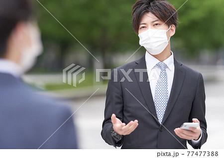 屋外で手振りをしながら会話するマスク姿のビジネスマン 77477388