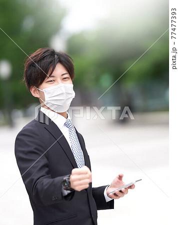 笑顔で拳を突き出すマスク姿のビジネスマン 77477393