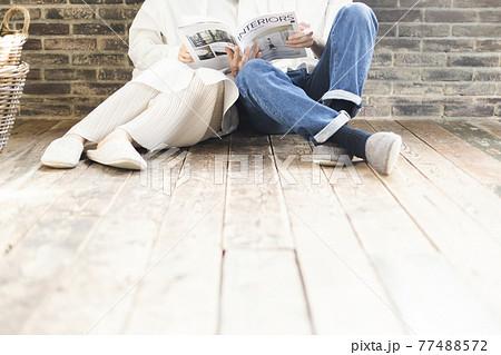 雑誌を見てくつろぐカップル 77488572