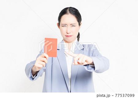 白バックの前に立って、レッドカードを示す女性 77537099