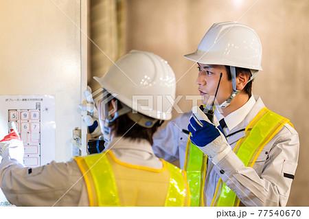 建設現場で配電盤を点検する作業員 77540670