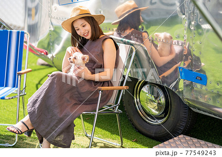 キャンピングカーで小型犬と暮らす若い女性 77549243