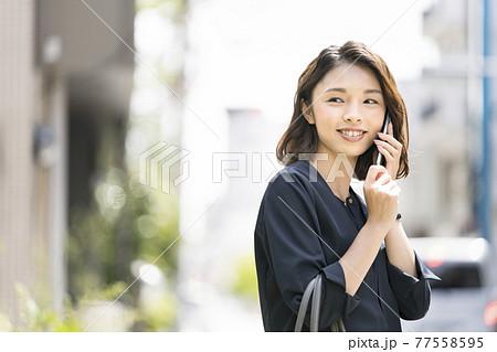 スマートフォンで通話する笑顔の女性 77558595