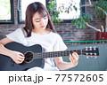 ギターを弾く若い女性 77572605