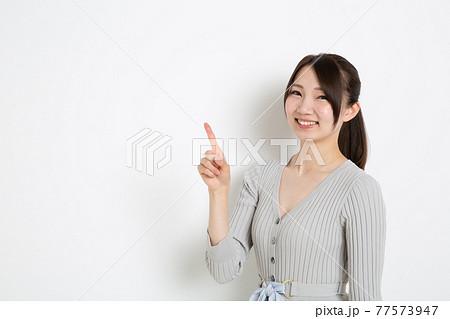 笑顔で指を1本立てているポニーテールの女性(コピースペース) 77573947