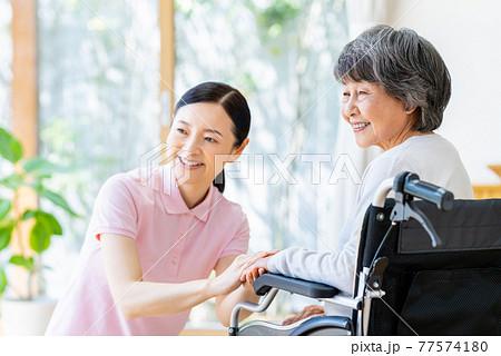 車椅子のシニアとミドルの介護福祉士 77574180