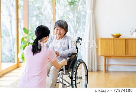 車椅子のシニアとミドルの介護福祉士 77574186